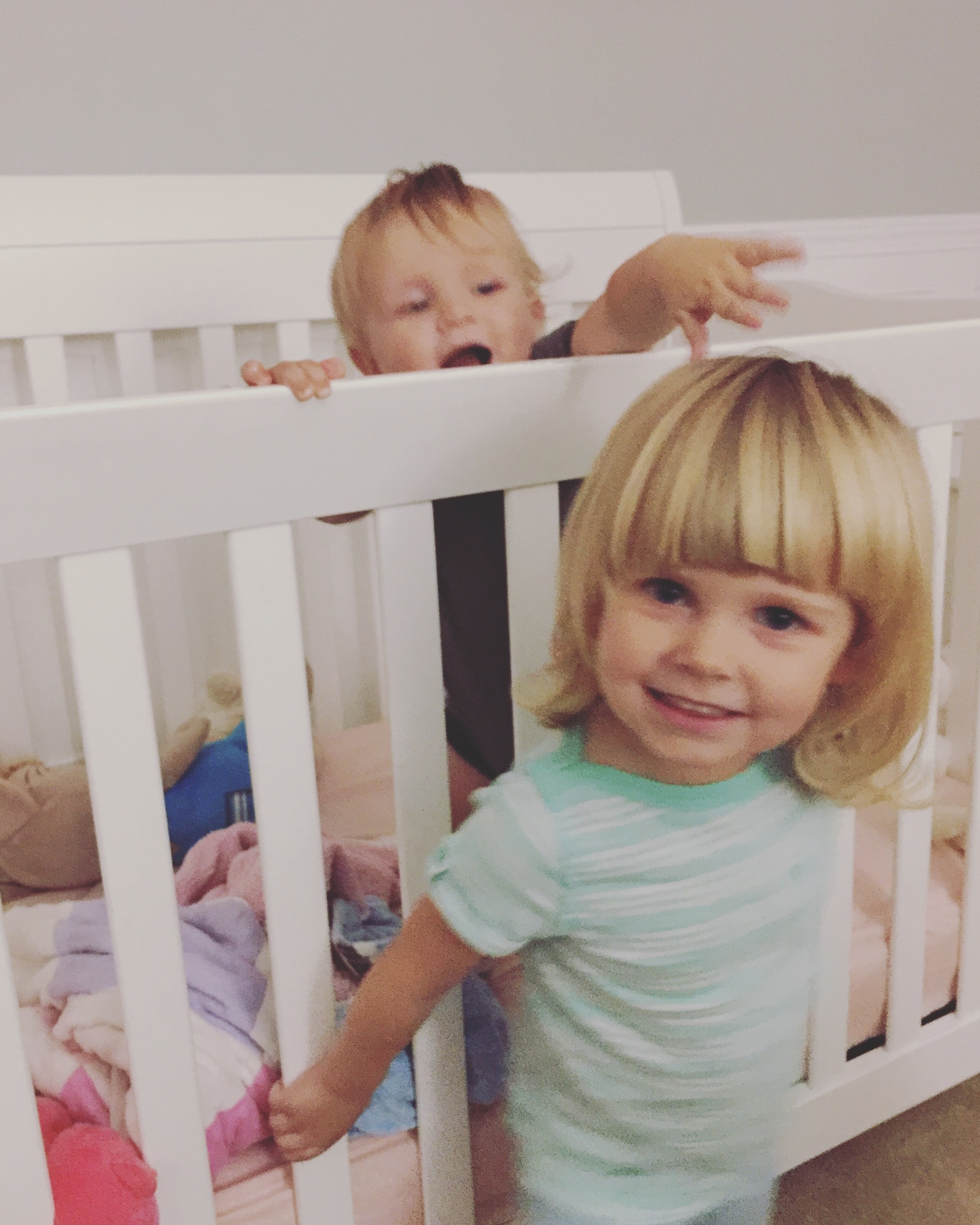 Two kiddos being crazy in a crib