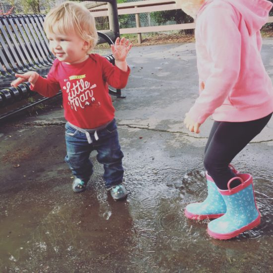 Two kids jumping in rain puddles