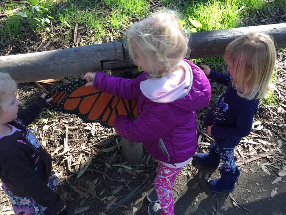 Toddlers play with butterfly prop at the Pismo Beach Monarch Butterfly Grove in San Luis Obispo County California.