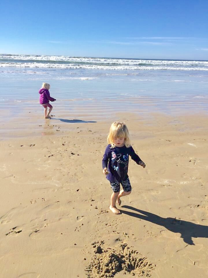Toddler girls run in sand on beach in Pismo Beach California