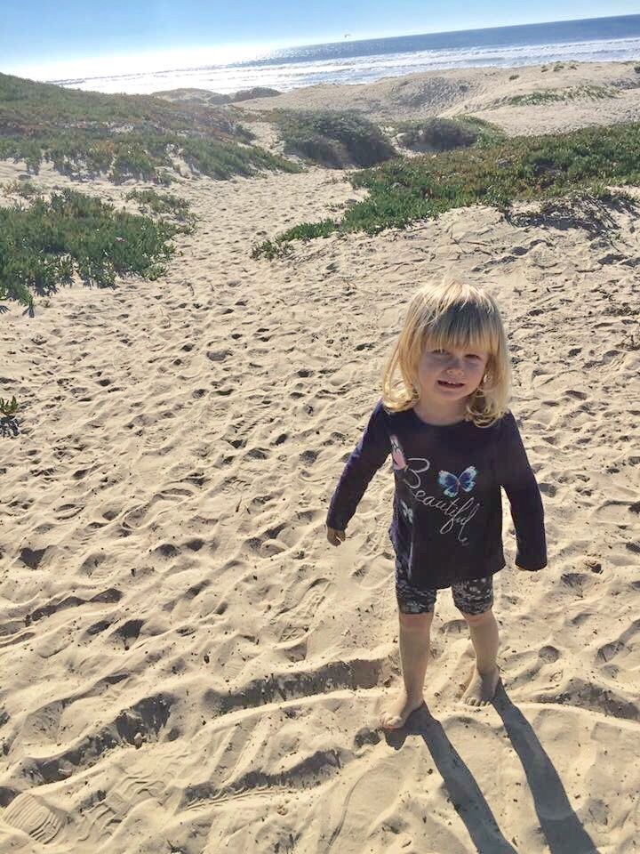 Toddler girl cries because she's wet and sandy in Pismo Beach California