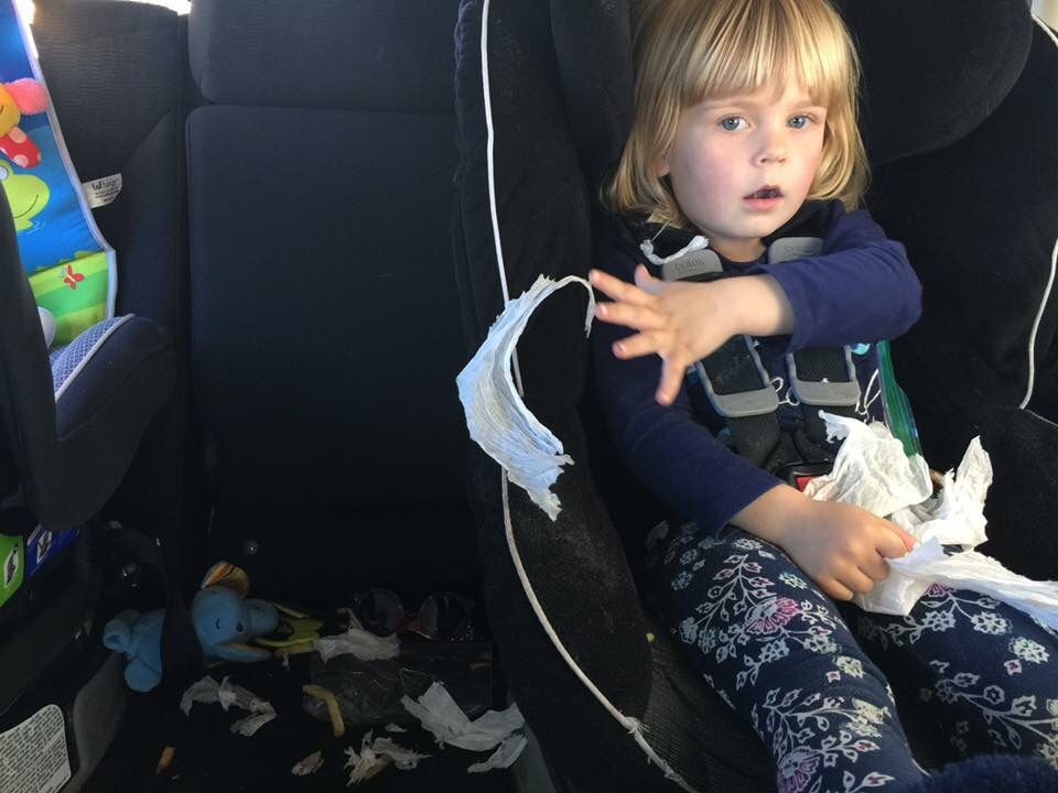 Tired toddler tearing up a napkin in the backseat of an SUV.