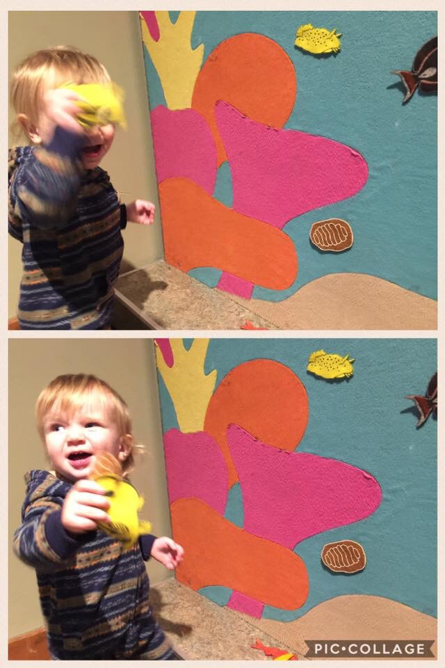 Baby boy jokes around with mom taking picture of him at the Seattle Aquarium's felt wall