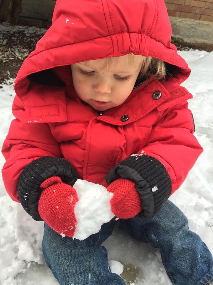 Baby boy makes his first snowball on Seattle snow day.
