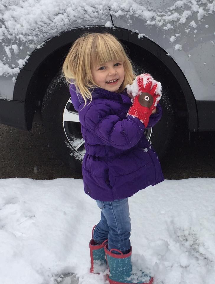 Toddler girl makes her first snowball on Seattle snow day.