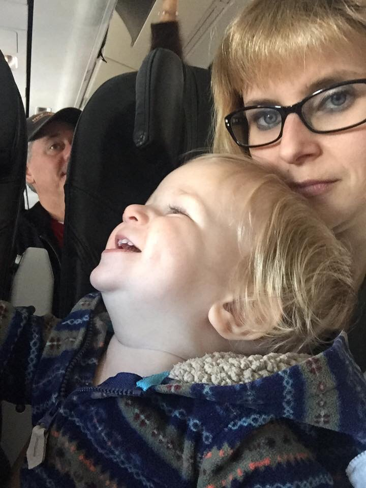 Tired af mom tries to entertain baby on a plane with Alaskan Airlines on flight to Seattle