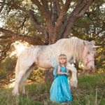 Toddler wears butterfly fairy princess costume to hang out with a unicorn