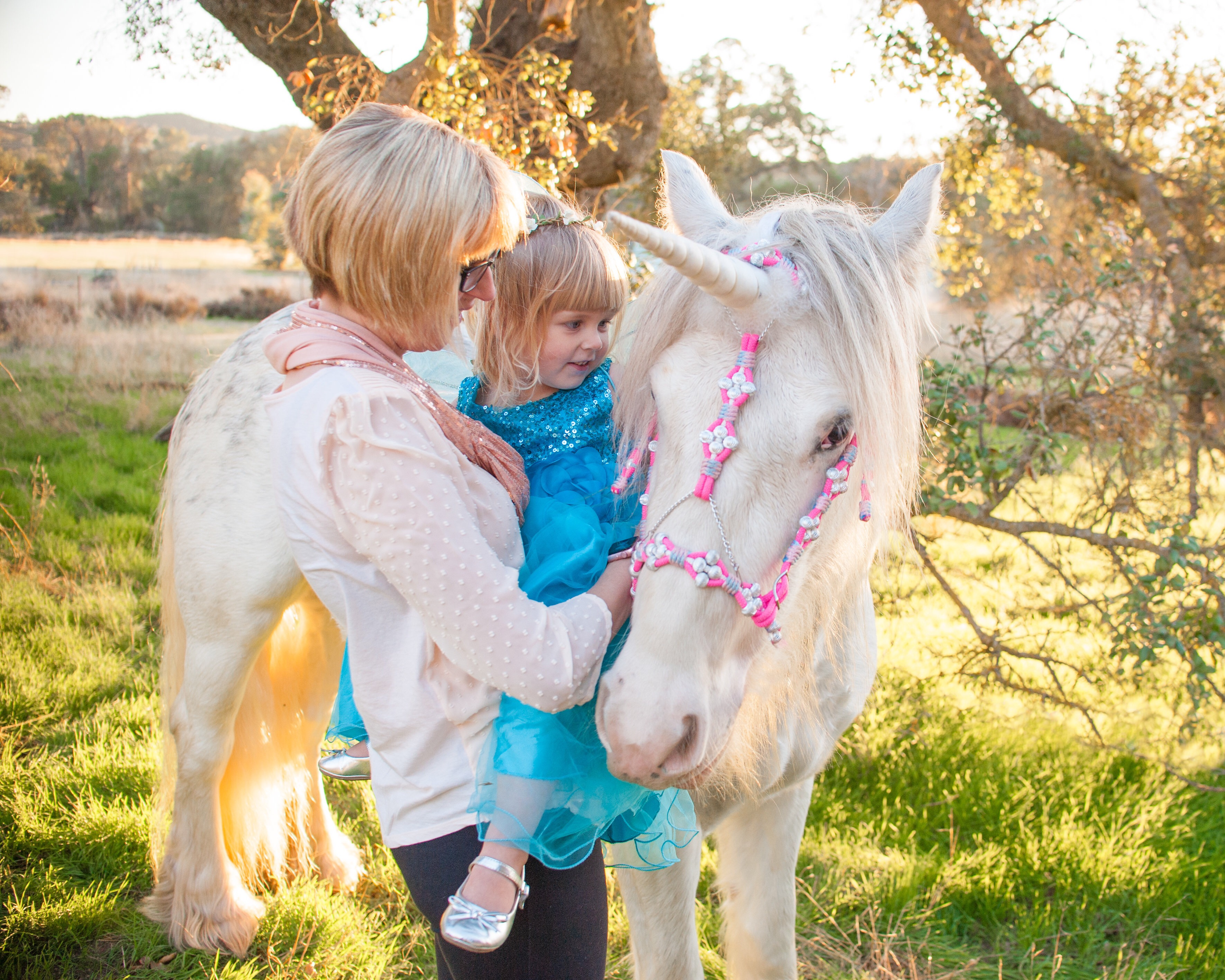 Mother and daughter stroke a unicorn's flowing white mane in Creston, California.
