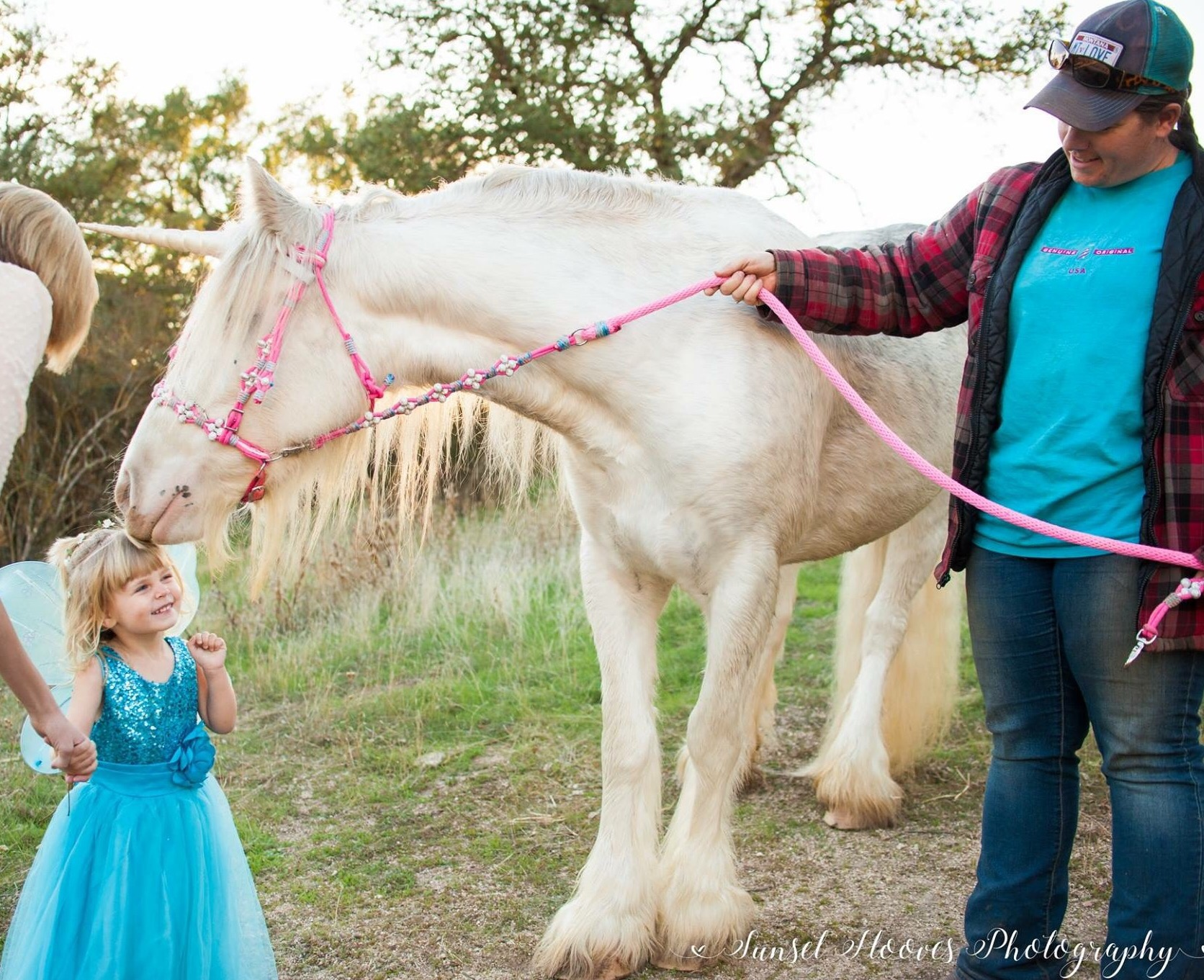 Magical unicorn nuzzles toddler dressed as a fairy princess in unicorn photoshoot in Creston, California.