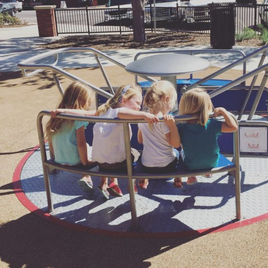 Friends on the New and modern merry-go-round at the Paso Robles Downtown City Park Playground