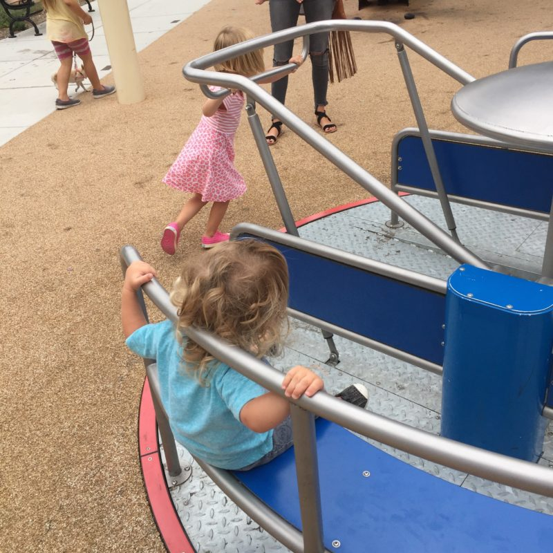 Kids pushing the new and modern merry-go-round at the Paso Robles Downtown City Park Playground
