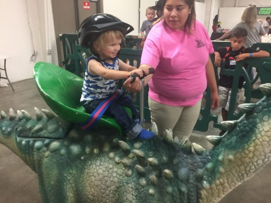 Baby on a walking dinosaur at Jurassic Quest Paso Robles