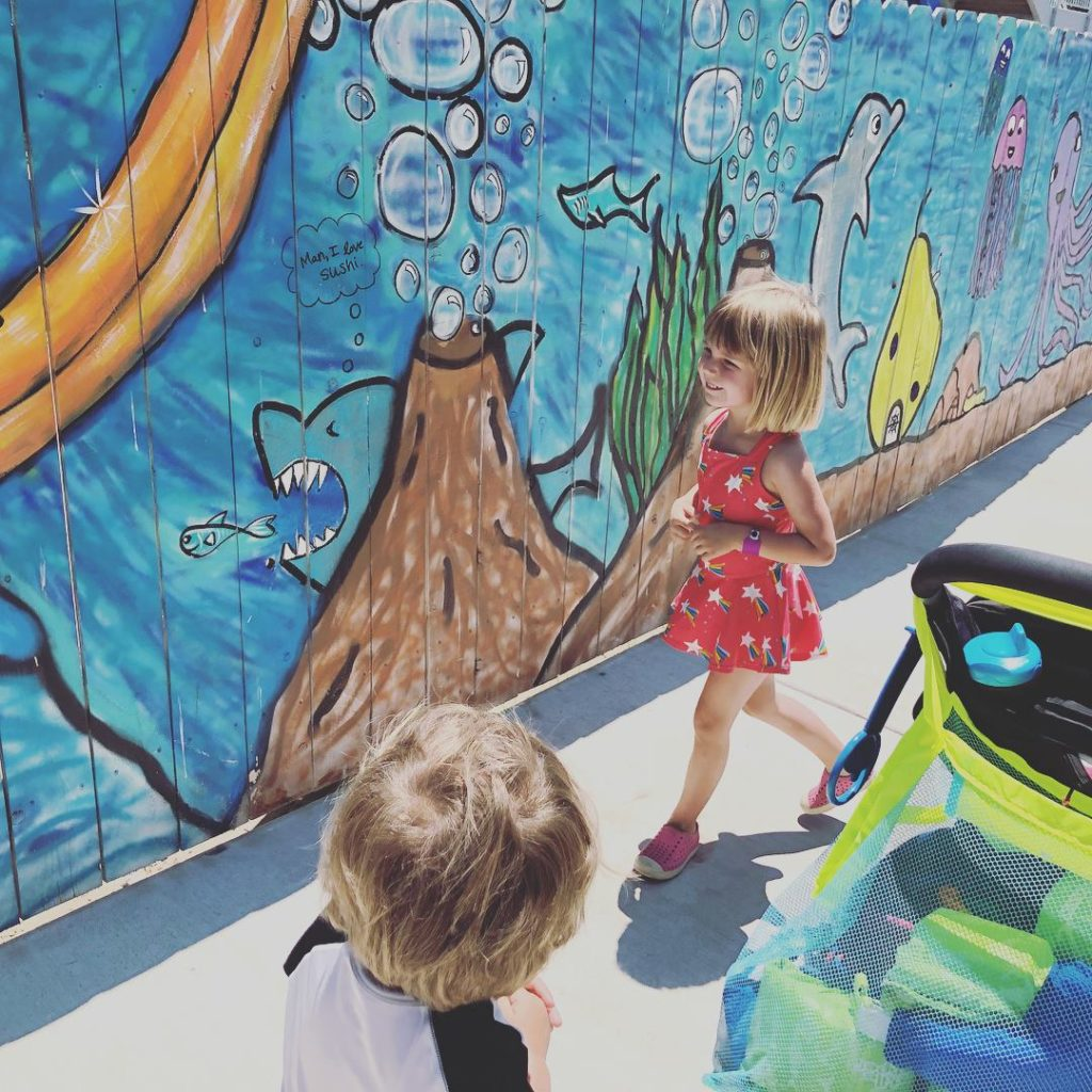 Two kids look at a waterpark mural