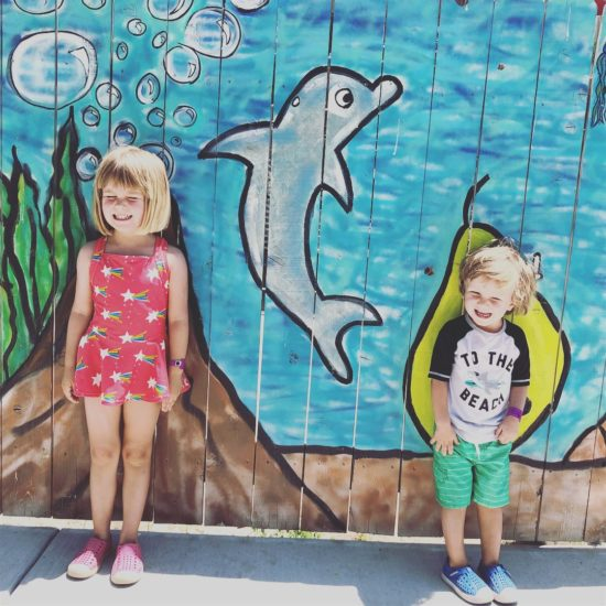 Two kids in front of wall mural with a painted dolphin