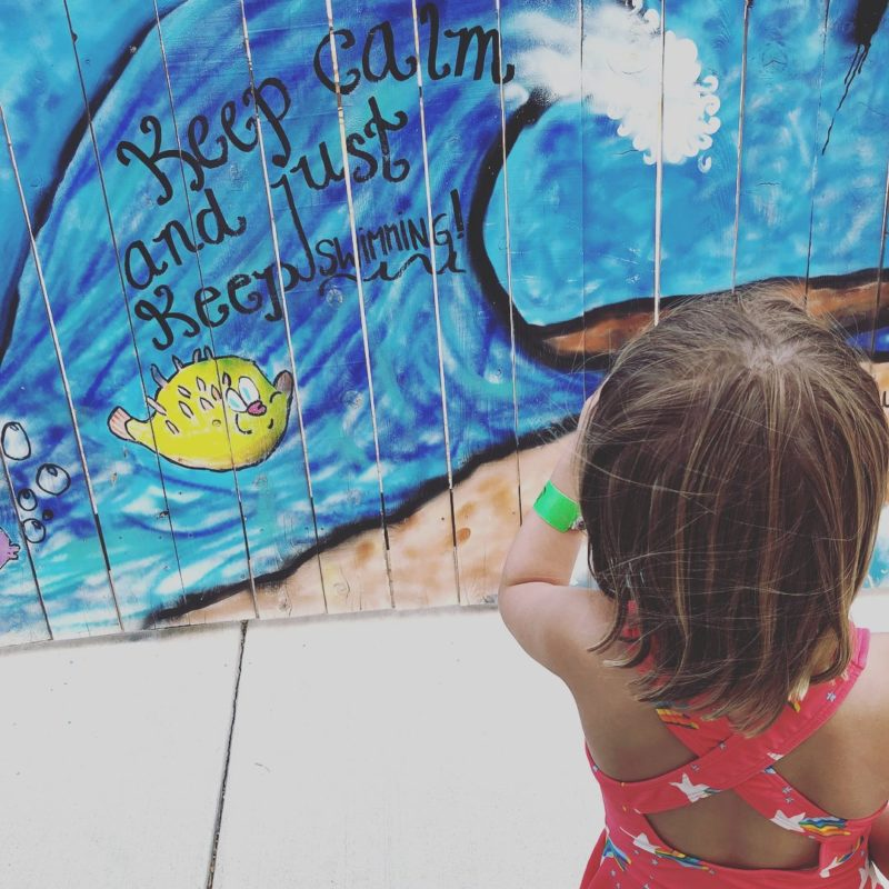 Little girl looking at a wall mural of a wave