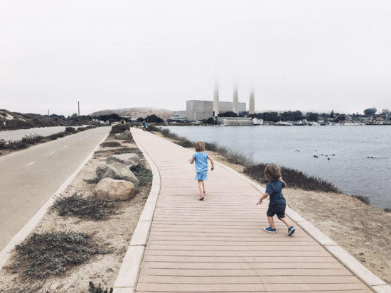 MORRO BAY HARBORWALKTwo In Tow & On The Go: A Family Adventure Column By Tonya Strickland __________________________________________________________________________ Two In Tow & On The Go is a SLO County Mommy Blog that details pictures, tips and stories about things to do with kids on California's Central Coast. Follow the adventure at @two.n.tow on Instagram and Facebook & at twontow.com. __________________________________________________________________________ On a whim, my 2 and 4 year old kiddos and I recently explored the Morro Bay HarborWalk. We were met with thrill-worthy beach swings, playful sea otters that tumbled and twirled in the calm harbor waters and boats that passed us as we ran along the expansive slated boardwalk. Kind of magical, right? This easy and free kidventure is a great way to get outside with a few key stops while you're there. Once you walk the HarborWalk, you'll find several lookout points, a slatted boardwalk and a Class 1 bike path away from the road. Between you start at the Embarcadero to the parking lot There are also two public restroom stops, a swing set and several lookout points with benches facing toward the calm waters. The humble beginnings of this stretch of Morro Bay was all just a vision In the early 1950s, according to the city. As the story goes, a Mr. Arthur E. Coleman worked to connect Morro Rock to the Embarcadero via a road to build a waterfront park for children. And that's just what exists today. Coleman Park features a fenced basketball court and six swings (including two bucket swings for the babes! The accompanying HarborWalk, completed about a decade ago, stretches from the Embarcadero's quaint string of gift/seafood/saltwater taffy shops to the iconic Morro Rock, the last in a line of volcanic earthly throwbacks reaching south toward San Luis Obispo. HarborWalk pairs a pedestrian walkway with slatted boards and a seperate, two-lane paved bike path for guests of all kinds. Even the crazy preschool-toddler variety. In fact, our favorite stop is a tie between the Coleman Park swingset and the playful otter pups swimming just south of the Rock As a bonus, it has lots of lookouts and views of harbor boats! And if you've studied up on your preschooler story books, you'll know them aaaall the boat names. And that's it! Easy-peasy. You could end your trip there, or go explore the Morro Bay Embarcadero which we detail in a Morro Bay Day Guide over on the blog, twontow.com; OR you can call it a success and just head home (I, personally, tend to not chance it with those tiny humans in tow). Either way, it will be fun day in Morro Bay. See you there!
