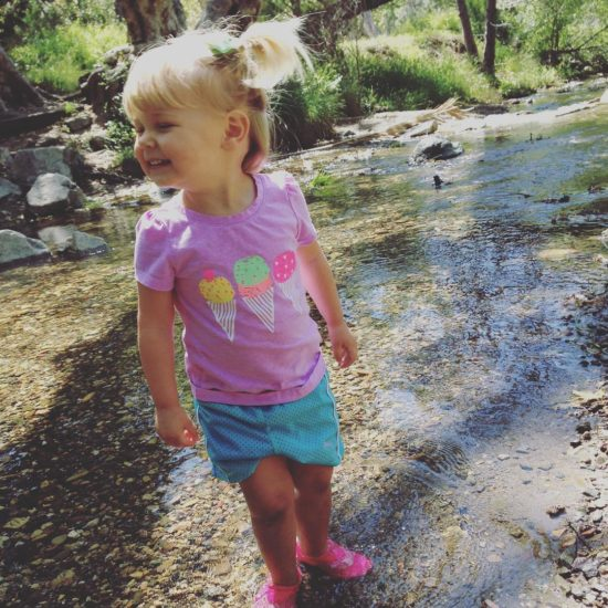 Little girl splashing in a creek