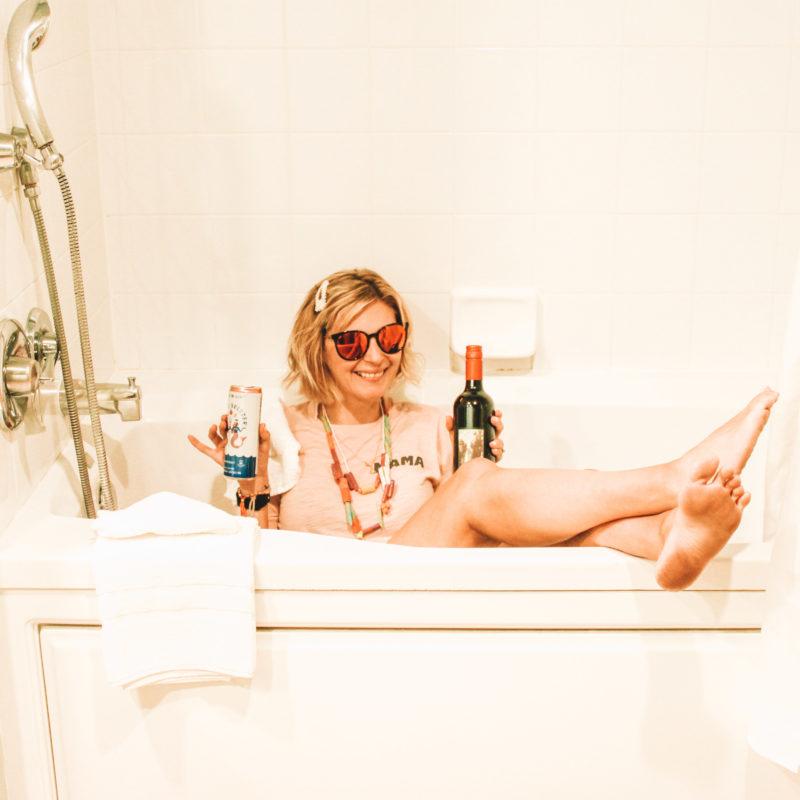 Girl in hotel bathroom joke posing with wine