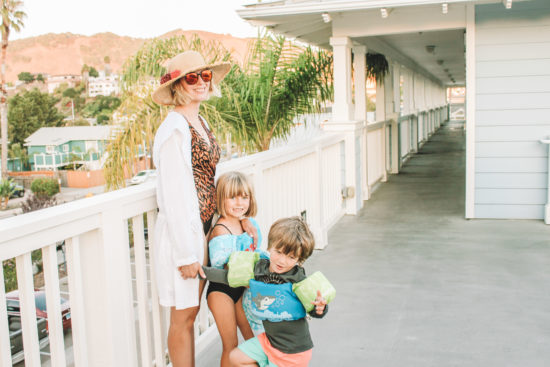 Mom posing in swimsuit and hat with kids at beach hotel