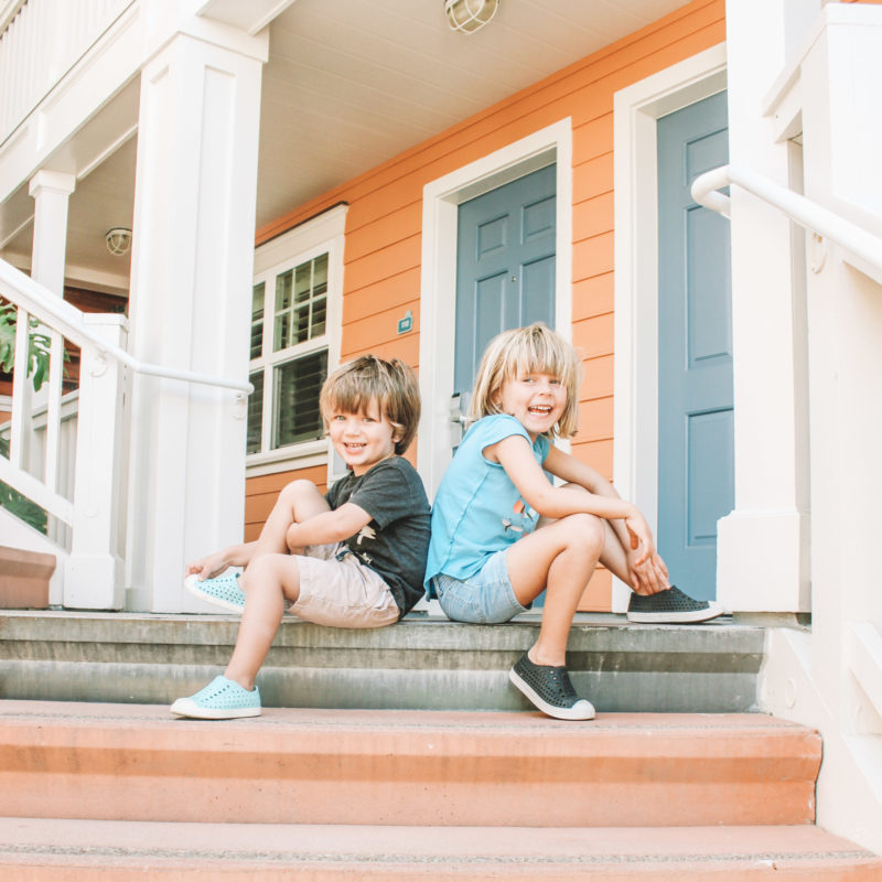Two kids pose on hotel steps