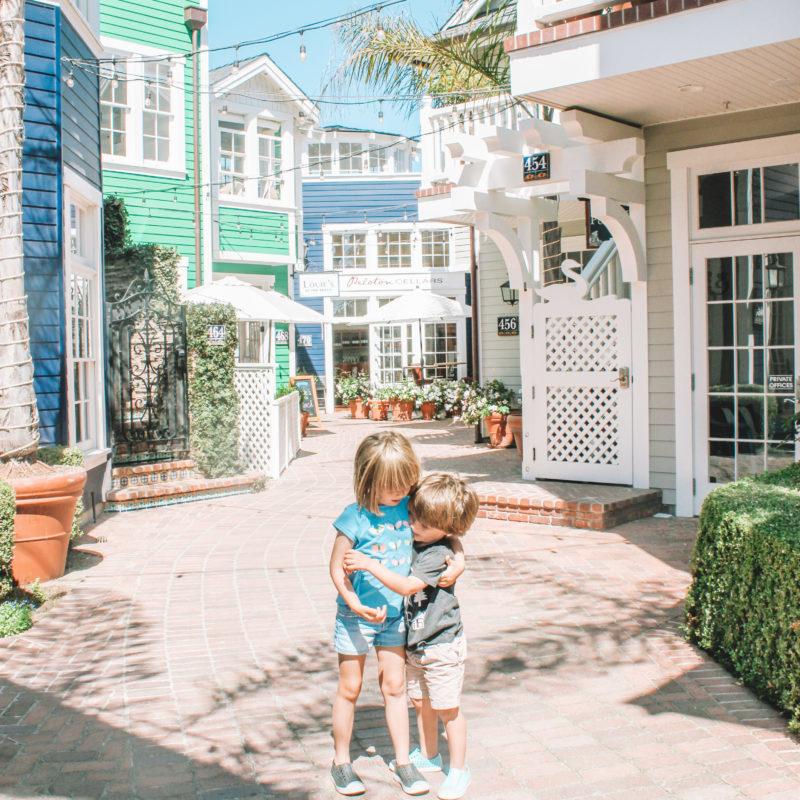 Two siblings hugging amid pretty painted buildings
