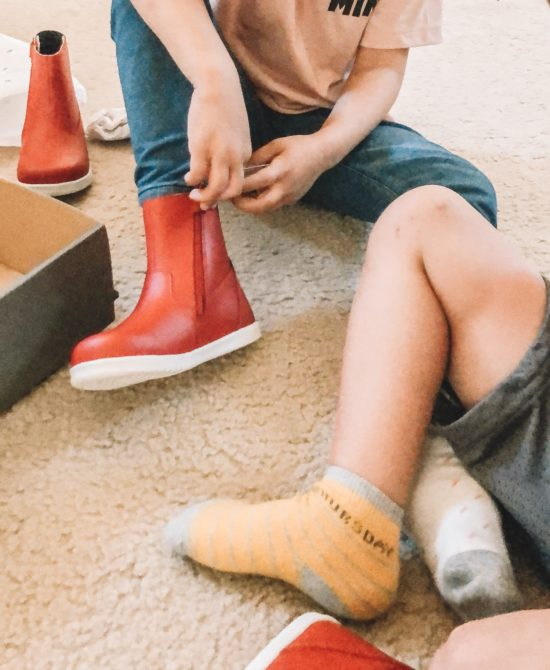 Girl putting on Bobux Paddington Red Boots in bedroom