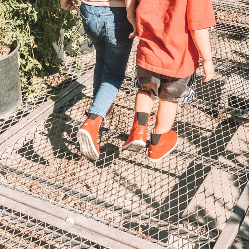 Closeup of kids wearing and walking in Bobux Paddington Red Boots