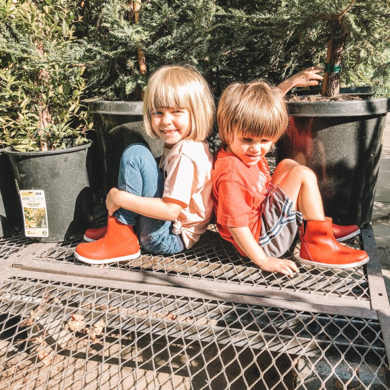 Boy and Girl in garden center wearing Bobux Paddington Red Boots