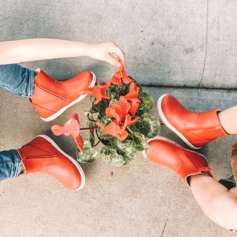 Bobux Paddington Red Boots on kids next to red flowers