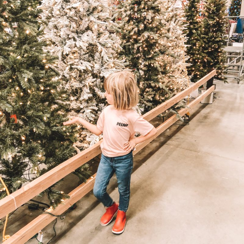 Girl looking at christmas trees in Bobux Paddington Red Boots