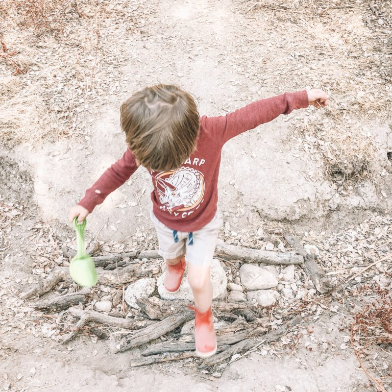 Little boy crossing a dry creek bed in Bobux Paddington Red Boots
