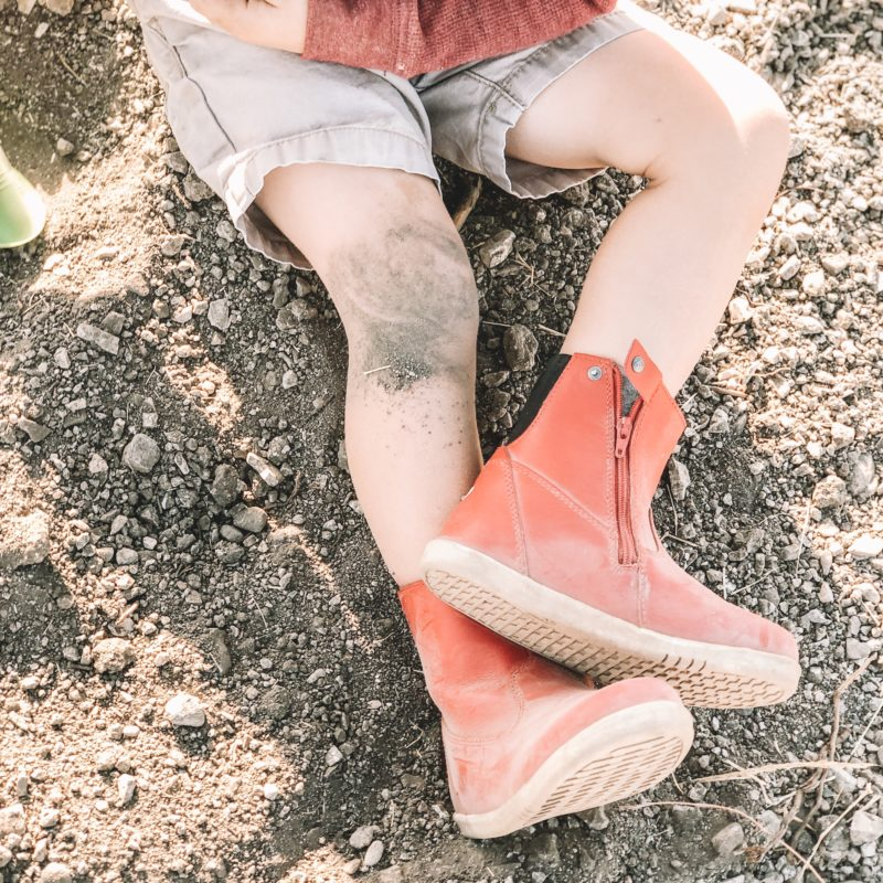 closeup in boy in dirt with Bobux Paddington Red Boot