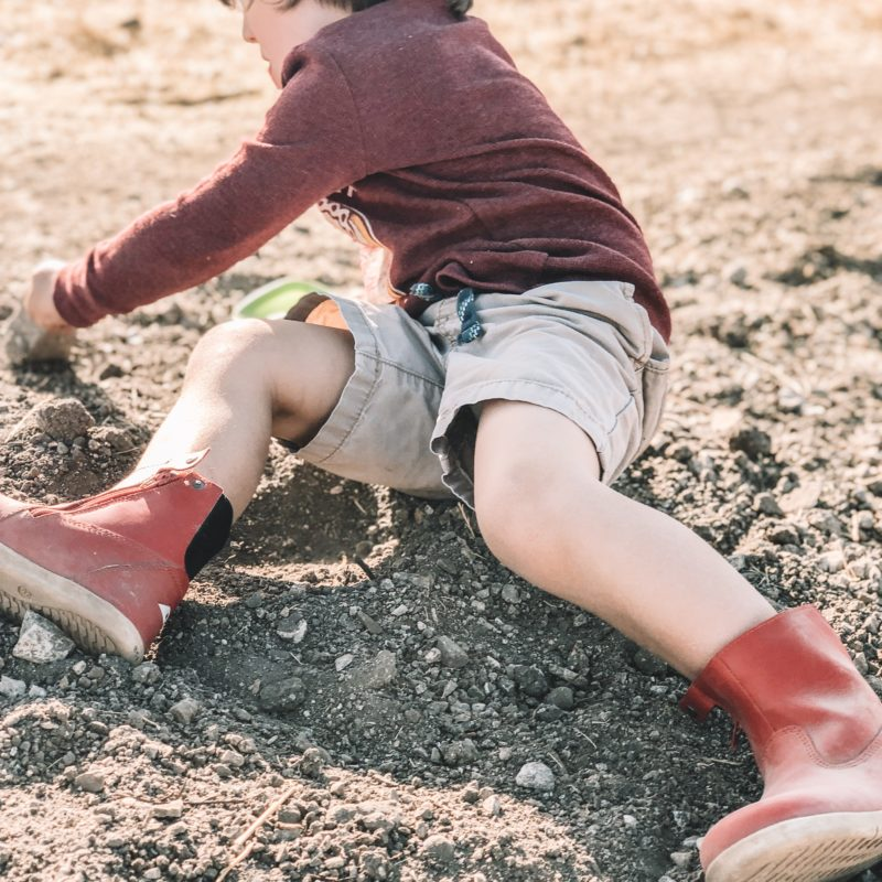 Little boy digging in dirt in Bobux Paddington Red Boot