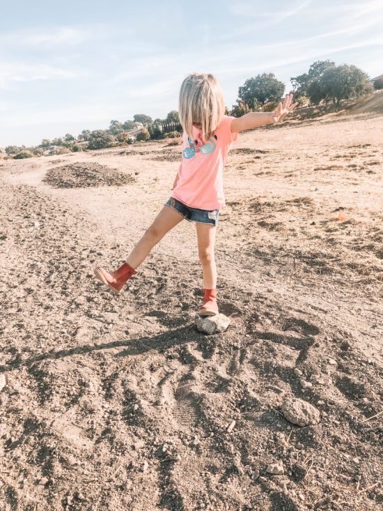 Girl standing on rock with Bobux Paddington Red Boot_3