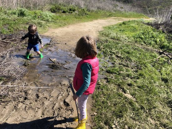 Kids walking in mud on hike