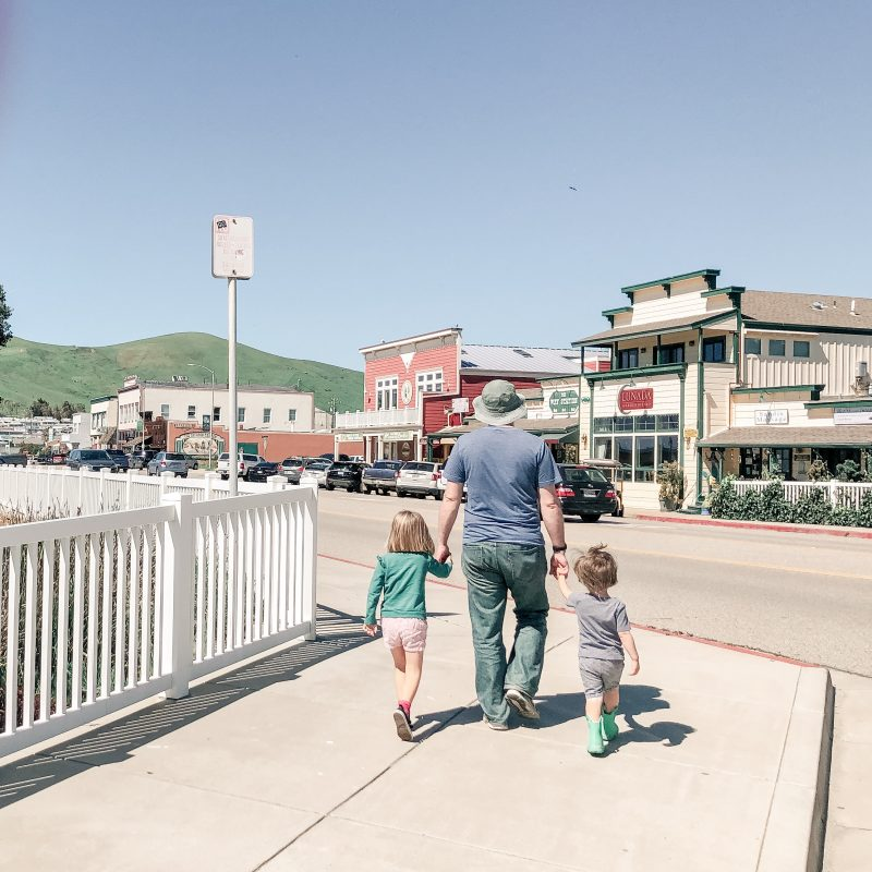 Dad and kids walking in a downtown setting