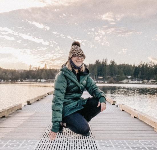 woman kneeling on pier under a beautiful sky