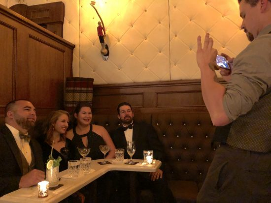 lavishly dressed group in dimly lit bar